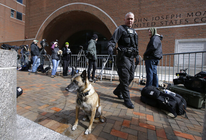 A Department of Homeland Security officer patrols with his K-9 outside federal court in Boston on Wednesday, April 3, 2019, where actress Felicity Huffman, actress Lori Loughlin and her husband, clothing designer Mossimo Giannulli are scheduled to attend an afternoon hearing in a nationwide college admissions bribery scandal. (AP Photo/Steven Senne)