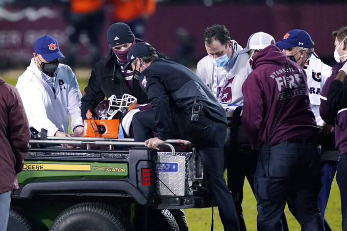 Medical personnel from both Mississippi State and Auburn lift injured Mississippi State defensive end Marquiss Spencer onto a cart during the second half of an NCAA college football game Saturday, Dec. 12, 2020, in Starkville, Miss. (AP Photo/Rogelio V. Solis)