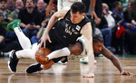 Boston Celtics guard Marcus Smart, bottom, tries to knock the ball away from Brooklyn Nets forward Rodions Kurucs (00) during the second half of an NBA basketball game in Boston, Monday, Jan. 7, 2019. (AP Photo/Charles Krupa)