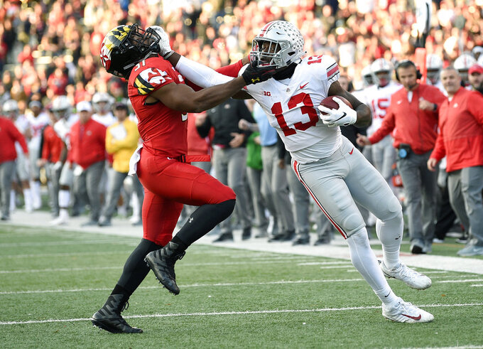 CORRECTS TO OVERTIME, NOT SECOND HALF - Ohio State tight end Rashod Berry (13) stiff arms Maryland linebacker Nnamdi Egbuaba (31) during overtime of an NCAA football game, Saturday, Nov. 17, 2018, in College Park, Md. Ohio State won 52-51 in overtime. (AP Photo/Nick Wass)