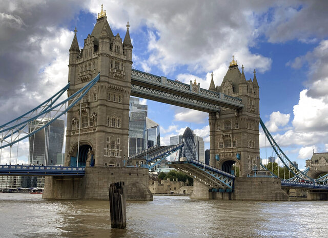 Tower Bridge crossing the River Thames is stuck open, leaving traffic in chaos and onlookers stunned as the iconic river crossing remains open, in London, Saturday Aug. 22, 2020.  The historic bridge has failed to close Saturday after opening to allow ships to pass underneath on the River Thames. (AP Photo / Tony Hicks)