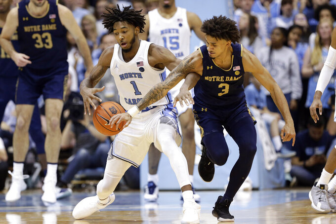 North Carolina guard Leaky Black (1) and Notre Dame guard Prentiss Hubb (3) chase the ball during the second half of an NCAA college basketball game in Chapel Hill, N.C., Wednesday, Nov. 6, 2019. North Carolina won 76-65. (AP Photo/Gerry Broome)