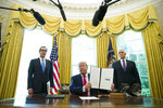 FILE - In this June 24, 2019, file photo, President Donald Trump holds up a signed executive order to increase sanctions on Iran, in the Oval Office of the White House in Washington, with Treasury Secretary Steven Mnuchin, left, and Vice President Mike Pence. The International Monetary Fund said in a report published Monday, Oct. 28, 2019, that political uncertainty and volatile oil prices are hindering economic growth in the Middle East this year. The region is reeling from U.S. sanctions on Iran and last month's attack on the world's largest oil processor in Saudi Arabia. (AP Photo/Alex Brandon, File)