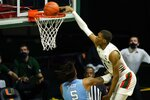 Miami forward Anthony Walker (1) dunks the ball over North Carolina forward Armando Bacot (5) during the second half of an NCAA college basketball game, Tuesday, Jan. 5, 2021, in Coral Gables, Fla.(AP Photo/Marta Lavandier)