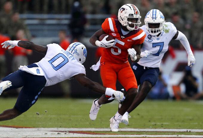 Virginia Tech's Raheem Blackshear (5) runs while pursued by North Carolina's Ja'Qurious Conley (0) and Eugene Asante (7) during the first half of an NCAA college football game Friday, Sept. 3, 2021, in Blacksburg, Va. (Matt Gentry/The Roanoke Times via AP)