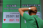 A man looks at an electronic board showing Hong Kong share index outside a bank In Hong Kong, Thursday, Oct. 11, 2018. Asian markets tumbled on Thursday, after Wall Street slumped on a heavy selling of technology and internet stocks. (AP Photo/Kin Cheung)
