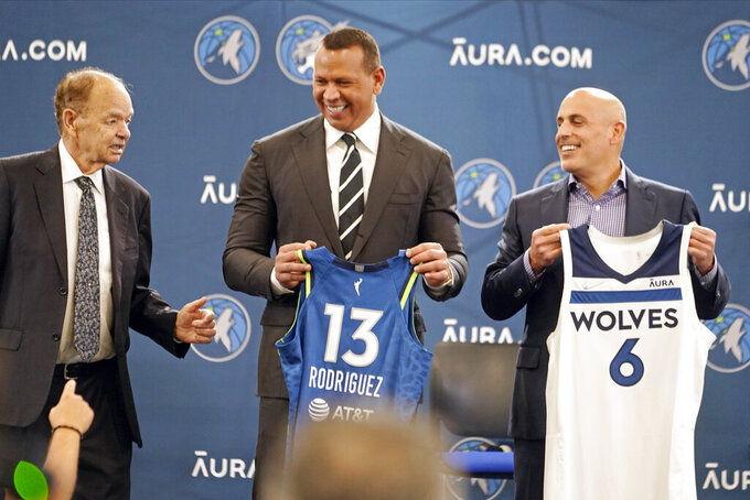 New Minnesota Timberwolves owners Marc Lore, right, and baseball great Alex Rodriguez, center, hold jerseys presented to them by team owner Glen Taylor during a new conference to introduce the new ownership partners of the NBA Timberwolves basketball team and the Minnesota Lynx of the WNBA, Monday, Sept. 27, 2021, in Minneapolis. (AP Photo/Jim Mone)
