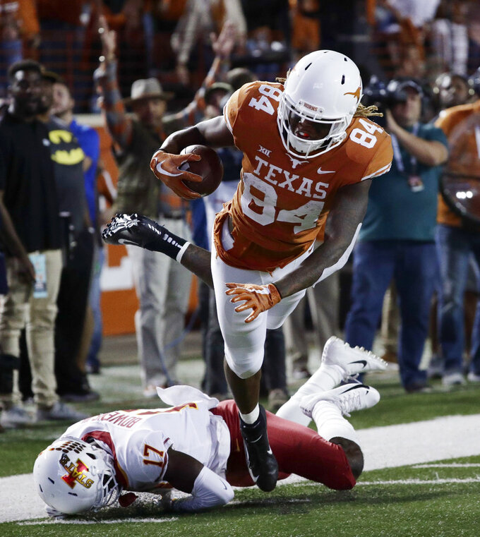 Texas wide receiver Lil'Jordan Humphrey (84) leaps over Iowa State defensive back Richard Bowens III (17) to score a touchdown on a 27-yard pass during the second half of an NCAA college football game, Saturday, Nov. 17, 2018, in Austin, Texas. (AP Photo/Eric Gay)