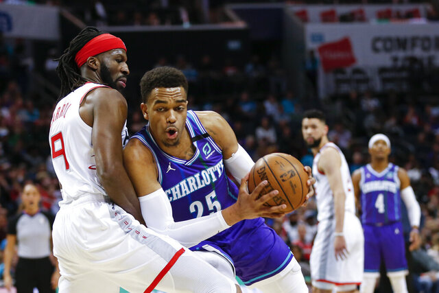 Charlotte Hornets forward P.J. Washington, right, drives into Houston Rockets forward DeMarre Carroll during the first half of an NBA basketball game in Charlotte, N.C., Saturday, March 7, 2020. (AP Photo/Nell Redmond)