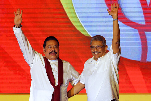 FILE - In this Aug. 11, 2019, file photo, Mahinda Rajapaksa, left, and his brother Gotabaya Rajapaksa wave to supporters during a party convention held to announce the presidential candidacy in Colombo, Sri Lanka. Sri Lanka's powerful, popular Rajapaksa brothers are likely to get strong support in parliamentary elections Wednesday that could add to their family political dynasty and their ability to amend the constitution. The prospect of those changes raise fears of weakening government institutions and the rule of law. The results of the vote could also lead to sibling rivalry, charting the country into more confusion, analysts say.. (AP Photo/Eranga Jayawardena, File)