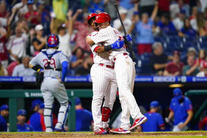 Philadelphia Phillies' Andrew Knapp, right, and Jean Segura celebrate after Knapp scored the game-winning run on a passed ball during the ninth inning of a baseball game against the Chicago Cubs, Wednesday, Sept. 15, 2021, in Philadelphia. (AP Photo/Matt Slocum)
