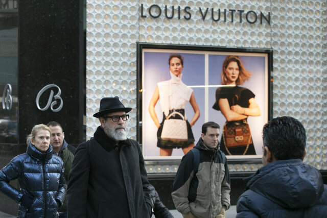 FILE - In this Nov. 25, 2019 file photo, pedestrians pass a store window for luxury brand Louis Vuitton, in New York. There are plenty of designer and luxury brands on the market, and in part because of Instagram's fashion bloggers and influencers, they're all the rage. Whether you want to invest in a quality item to last for years or you just want to treat yourself to a luxury label every once in a while, you can reduce your costs by shopping secondary markets or outlet stores.  (AP Photo/Mark Lennihan, File)