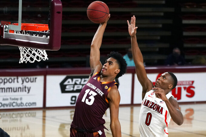 Arizona State guard Josh Christopher (13) dunks in front of Arizona guard Bennedict Mathurin during the first half of an NCAA college basketball game Thursday, Jan. 21, 2021, in Tempe, Ariz. (AP Photo/Rick Scuteri)