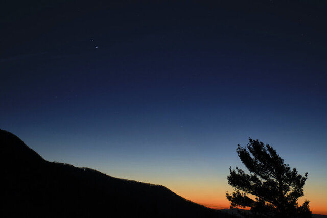 In this Sunday, Dec. 13, 2020 photo made available by NASA, Saturn, top, and Jupiter, below, are seen after sunset from Shenandoah National Park in Luray, Va. The two planets are drawing closer to each other in the sky as they head towards a