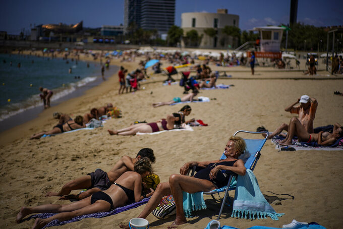 """People sunbathe on the beach in Barcelona, Spain, Friday, July 9, 2021. Spain's top diplomat is pushing back against French cautions over vacationing on the Iberian peninsula. Southern Europe's holiday hotspots worry that repeated changes to rules on who can visit is putting people off travel. On Thursday, France's secretary of state for European affairs, Clement Beaune, advised people to """"avoid Spain and Portugal as destinations"""" when booking their holidays because COVID-19 infections are surging there. (AP Photo/Joan Mateu)"""