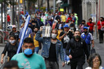 Shoppers and commuters walk along a sidewalk in central Mexico City, Monday, July 6, 2020. After three months of shutdown, officials allowed a partial reopening of the downtown commercial area last week, although COVID-19 cases continue to climb.(AP Photo/Rebecca Blackwell)