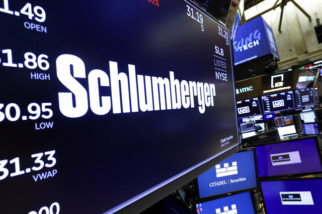 FILE - In this Oct. 8, 2019 file photo, the logo for Schlumberger appears above a trading post on the floor of the New York Stock Exchange.   Schlumberger is cutting more than 21,000 jobs and paying $1.02 billion in severance as declining oil prices amid the coronavirus pandemic push it to slash costs  Schlumberger Ltd. said in a regulatory filing on Friday, July 24, 2020, that vast majority of the severance charge is expected to be paid out during the second half of the year.  (AP Photo/Richard Drew, File)