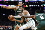 Boston Celtics' Jayson Tatum drives between Milwaukee Bucks' Eric Bledsoe (6) and Brook Lopez during the first quarter of an NBA basketball game Wednesday, Oct. 30, 2019, in Boston. (AP Photo/Winslow Townson)