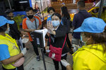 A passenger of a bus reaches to check her body temperature at roadside check point in the border of Samut Sakhon province and Bangkok in Thailand, Monday, Jan. 4, 2021. For much of 2020, Thailand had the coronavirus under control. After a strict nationwide lockdown in April and May, the number of new local infections dropped to zero, where they remained for the next six months. However, a new outbreak discovered in mid-December threatens to put Thailand back where it was in the toughest days of early 2020. (AP Photo/Gemunu Amarasinghe)