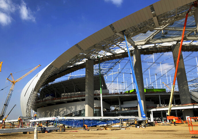 Workers and cranes continue construction on the south entrance to SoFi Stadium in Inglewood, Calif., on Wednesday, Jan. 22, 2020. The estimated $5 billion project is on schedule to open in July as the most expensive stadium in NFL history. (AP Photo/Greg Beacham)