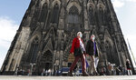 People are ordered to wear face masks in front of the famous Cathedral in Cologne, Germany, Thursday, Oct. 22, 2020. The city exceeded the important warning level of 50 new infections per 100,000 inhabitants in seven days. More and more German cities become official high risk corona hotspots with travel restrictions within Germany. (AP Photo/Martin Meissner)