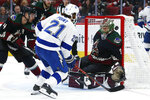 Tampa Bay Lightning center Brayden Point (21) scores a goal against Arizona Coyotes goaltender Antti Raanta, right, as Coyotes defenseman Niklas Hjalmarsson (4) watches during the second period of an NHL hockey game Saturday, Feb. 22, 2020, in Glendale, Ariz. (AP Photo/Ross D. Franklin)