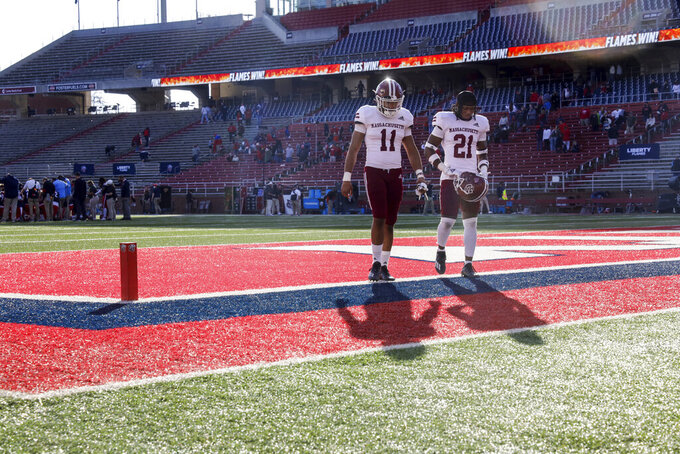 Massachusetts wide receiver Javon Turner (11) and Te'Rai Powell (21) walk off the field following their loss in an NCAA college football against Liberty on Friday, Nov. 27, 2020, at Williams Stadium in Lynchburg, Va. (AP Photo/Shaban Athuman)