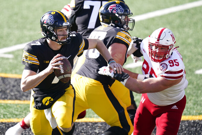 Iowa quarterback Spencer Petras (7) runs from Nebraska defensive lineman Ben Stille (95) during the first half of an NCAA college football game, Friday, Nov. 27, 2020, in Iowa City, Iowa. (AP Photo/Charlie Neibergall)