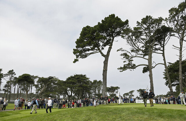 FILE - In this  Saturday, May 2, 2015 file photo, Rory McIlroy, left, of Northern Ireland, and Hideki Matsuyama, right, of Japan, make their way down the fairway after hitting from the eighth tee of TPC Harding Park at the Match Play Championship in San Francisco. Harding Park hosts the PGA Championship on Aug. 6-9, the first major without spectators.  (AP Photo/Eric Risberg, File)
