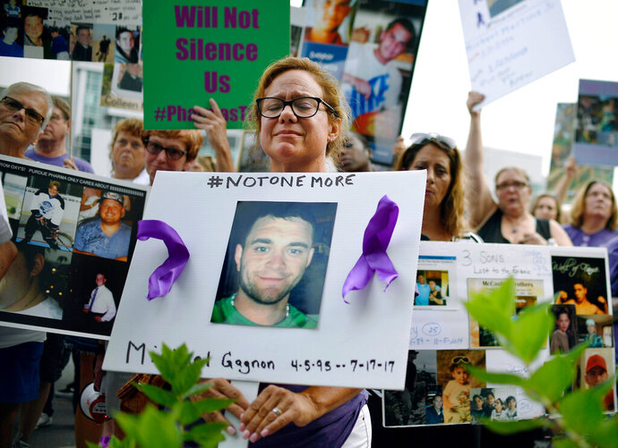 FILE - In this Friday, Aug. 17, 2018, file photo, Christine Gagnon of Southington, Conn., protests with other family and friends who have lost loved ones to OxyContin and opioid overdoses at Purdue Pharma LLP headquarters in Stamford, Conn. Gagnon lost her son Michael 13 months earlier. OxyContin maker Purdue Pharma is expected to file for bankruptcy after settlement talks over the nation's deadly overdose crisis hit an impasse, attorneys general involved in the talks said Saturday, Sept. 7, 2019, in a message to their counterparts across the country. (AP Photo/Jessica Hill, File)
