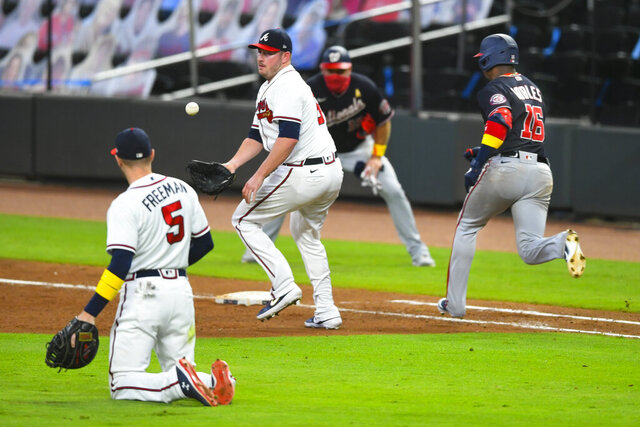 Atlanta Braves relief pitcher Tyler Matzek, center, cannot get a glove on a toss from first baseman Freddie Freeman (5) as Washington Nationals' Victor Robles (16) runs safely to first on a one-run bunt during the sixth inning of a baseball game Saturday, Sept. 5, 2020, in Atlanta. (AP Photo/John Amis)