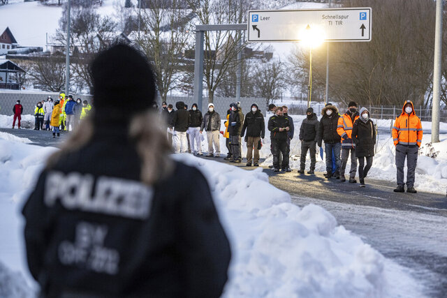 Numerous people wait in front of a Corona test station at the German-Czech Republic border in Furth im Wald, Germany, Monday, Jan. 25, 2021. German police say hundreds of cars and pedestrians are lining up at border crossings along the Czech-German border after Germany declared the Czech Republic a high risk area in the pandemic meaning it requires proof a negative coronavirus test results before entry. (Armin Weigel/dpa via AP)