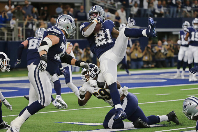 Dallas Cowboys running back Ezekiel Elliott (21) is tripped by Los Angeles Rams defensive tackle Sebastian Joseph-Day (69) following a reception in the first half of an NFL football game in Arlington, Texas, Sunday, Dec. 15, 2019. (AP Photo/Michael Ainsworth)