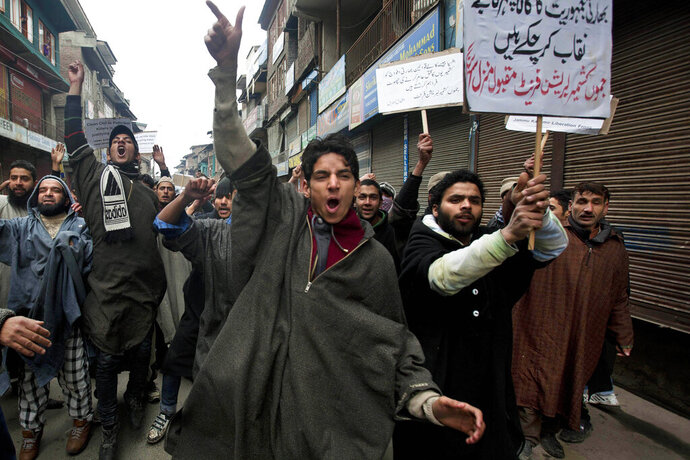 FILE - In this Friday, Jan. 31, 2014, file photo, Activists of Jammu Kashmir Liberation Front (JKLF) shout slogans during a protest against the Indian army's decision to close a fake encounter case against five soldiers in connection with the killing of five Kashmiris in Pathribal in March 2000, in Srinagar, India. In a separate case, the Indian military on Friday, Sept. 18, said its soldiers in Kashmir exceeded their legal powers in the killings of three local men it had described as Pakistani terrorists on July 18, 2020. Police ordered an investigation into the accusation of a staged gunbattle, and the results have not yet been released. The results of the police probe are likely to spark an outcry among Kashmiri activists who for years have accused Indian troops of abusing their powers and repeatedly targeting civilians. Placard at background right reads,