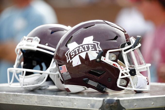 FILE - This is an April 21, 2018, file photo showing Mississippi State football helmets on the sideline during the second half of Mississippi State's Maroon and White spring NCAA college football game, in Starkville, Miss. Mississippi State has received three years' probation from the NCAA after an investigation determined a part-time student tutor completed coursework for 10 football players and one men's basketball player in an online class. (AP Photo/Rogelio V. Solis, File)