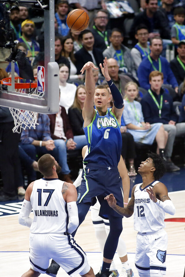 Dallas Mavericks forward Kristaps Porzingis (6) shoots the three-point basket over Memphis Grizzlies center Jonas Valanciunas (17) and guard Ja Morant (12) during the first half of an NBA basketball game in Dallas, Friday, March 6, 2020. (AP Photo/Ray Carlin)