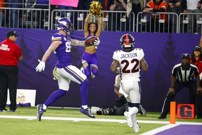 Minnesota Vikings tight end Kyle Rudolph catches a 32-yard touchdown pass in front of Denver Broncos strong safety Kareem Jackson (22) during the second half of an NFL football game, Sunday, Nov. 17, 2019, in Minneapolis. (AP Photo/Bruce Kluckhohn)