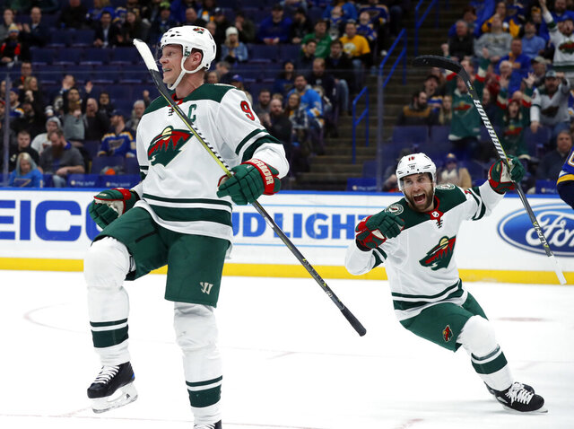 FILE - In this Feb. 6, 2018, file photo, Minnesota Wild's Mikko Koivu, of Finland, celebrates after scoring as teammate Jason Zucker, right, watches during the first period of an NHL hockey game against the St. Louis Blues, in St. Louis. Koivu's extraordinary career with the Minnesota Wild is over. General manager Bill Guerin said Friday, Sept. 18, 2020, the team will not resign the 37-year-old Finn, whose contract is expiring.(AP Photo/Jeff Roberson, File)