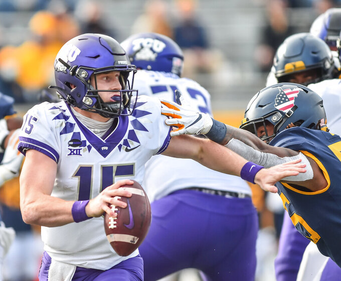 TCU  quarterback Max Duggan (15) scrambles to avoid the sack by West Virginia defensive lineman Dante Stills (55) during the second half of an NCAA college football game on Saturday, Nov. 14, 2020, in Morgantown, W.Va. (William Wotring/The Dominion-Post via AP)