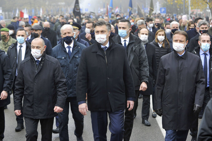 Croatia's Prime Minister Andrej Plenkovic, center, takes part in a commemoration march in Vukovar, Croatia, Wednesday, Nov. 18, 2020. Some thousands marched to commemorate the suffering of Croatia's eastern city of Vukovar during the 1991-95 war despite a continuously high number of infection and fatalities from the new coronavirus. (AP Photo)