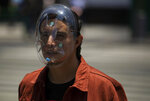 A pedestrian wears a makeshift face mask as a precaution against the spread of COVID-19, in downtown Mexico City, Friday, July 3, 2020. Limited reopening of restaurants and other businesses in the capital this week came as new coronavirus cases continued to climb steadily. (AP Photo/Fernando Llano)