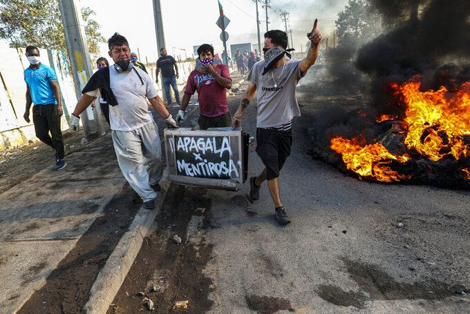 """Protesters carry a damaged television spray painted with a message that reads in Spanish: """"Turn it off for being a liar,"""" directed at local news channels, past a burning barricade during a protest demanding food aid from the government amid the new coronavirus pandemic, at the 17 de Mayo neighborhood, in Santiago, Chile, Tuesday, May 26, 2020. Protesters are complaining about the lack of resources to deal with the COVID-19 pandemic. (AP Photo/Esteban Felix)"""