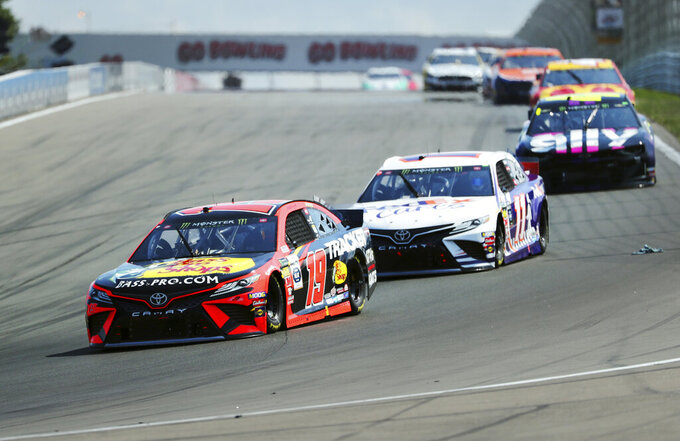Martin Truex, Jr., and Denny Hamlin head into Turn 1 during a NASCAR Cup Series auto race at Watkins Glen International, Sunday, Aug. 4, 2019, in Watkins Glen, N.Y. (AP Photo/John Munson)