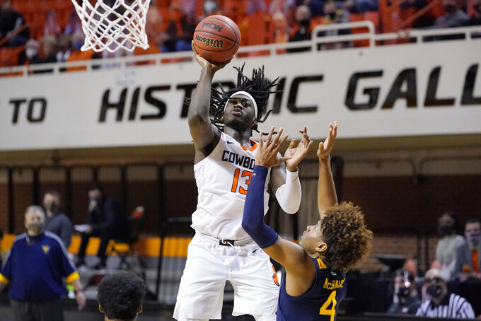 Oklahoma State guard Isaac Likekele (13) shoots over West Virginia guard Miles McBride (4) in the second half of an NCAA college basketball game Monday, Jan. 4, 2021, in Stillwater, Okla. (AP Photo/Sue Ogrocki)