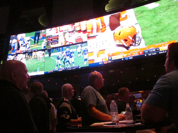 Customers watch an NFL game in the sports betting lounge at the Ocean Resort Casino in Atlantic City N.J. on Sept. 9, 2018. The coronavirus outbreak has added new wrinkles for bettors this year, but even so, the nation's sportsbooks expect a record year of bets on football in 2020 from an antsy public that has been cooped up for months amid the pandemic. (AP Photo/Wayne Parry)