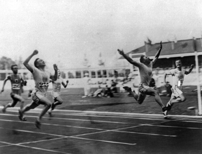 "FILE - In this 1920 file photo, Charles (Charley) Paddock, second from right, of the USA wins the 100 meters final with his famous ""flying finish"" at the 1920 Summer Olympics in Antwerp, Belgium. Morris Kirksey, far right, of the USA was second, and Jackson Scholz of USA, left, was fourth. Third place Harry Edward not shown. (AP Photo/File)"