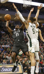 Brooklyn Nets' Treveon Graham, left, shoots against the Milwaukee Bucks' D. J. Wilson, right, during the second half of an NBA basketball game Saturday, April 6, 2019, in Milwaukee. (AP Photo/Jeffrey Phelps)
