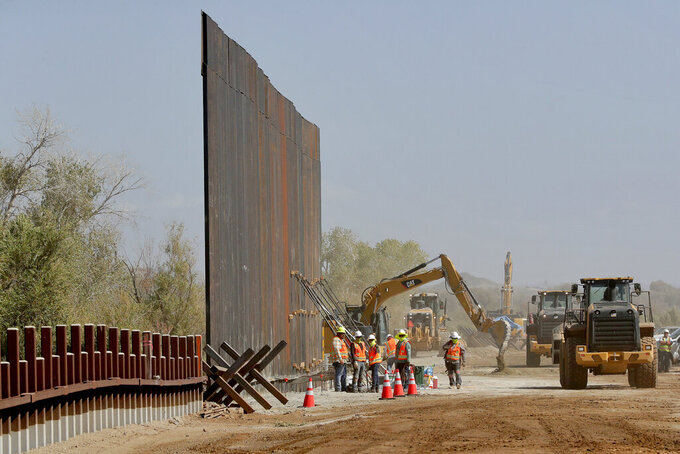FILE - Contractors erect a section of border wall, replacing smaller fortifications, Tuesday, Sept. 10, 2019, along the Colorado River in Yuma, Ariz. Top Trump administration officials will visit South Texas five days before Election Day to announce they have completed 400 miles of U.S.-Mexico border wall, attempting to show progress on perhaps the president's best-known campaign promise four years ago. But most of the wall went up in areas that already had smaller barriers. (AP Photo/Matt York)