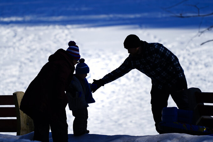 FILE - In this Feb. 5, 2021 file photo, a couple helps a child on a snow covered embankment at in Huntingdon Valley, Pa.   The cost to adopt a child can range from $20,000 to $45,000, according to the Child Welfare Information Gateway. Each year, millions of families navigate the expense and a process that can be overwhelming for prospective adoptive parents who aren't familiar with the steps or fees involved. (AP Photo/Matt Rourke)