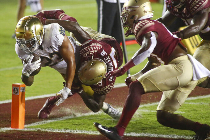 Notre Dame running back Kyren Williams (23) scores a touchdown as Florida State defensive back Jarvis Brownlee, Jr. (3) hangs onto him in the third quarter of an NCAA college football game Sunday, Sept. 5, 2021, in Tallahassee, Fla. (AP Photo/Phil Sears)